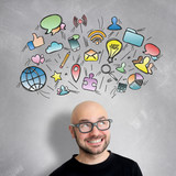 Multimedia icons going out of the head of a young attractive smiling man geek with glasses