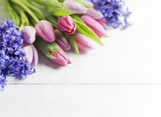 Beautiful pink tulips and hyacinths on white-plank background