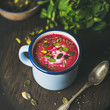 Spring detox beetroot soup with mint, pistachio, chia, flax, pumpkin seeds in blue enamel mug over dark wooden background, square crop. Clean eating, healthy, vegetarian, vegan, dieting concept