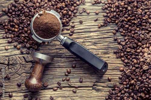 Coffee.Coffee beans and portafilter on old oak wooden table.
