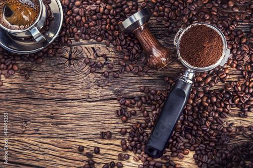 Kawa. Czarna kawa z ziaren kawy i portafilter na starym drewnianym stole dębu.