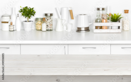 Wooden planks table over blurred image of kitchen bench interior