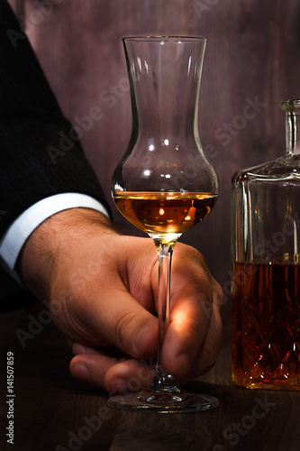 Hand of a man holding a glass of tulip with whiskey beside stands a decanter on a wooden table