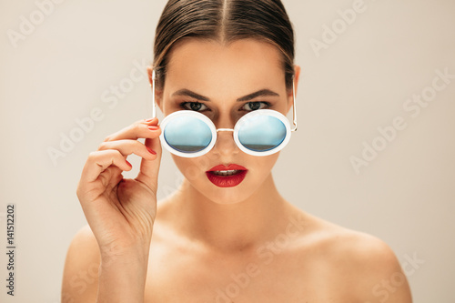 Plakat Fashion woman peeking over sunglasses