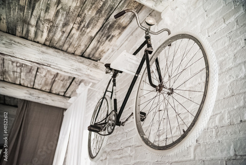 Old white bicycle whist on a white stone wall. Details of the old bicycle.
