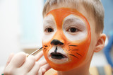 Make up artist making tiger mask for child.Children face painting. Boy painted as tiger or ferocious lion. Preparing for theatrical performance. Boy actor playing role. Tiger mask face - 141525674