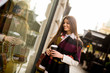Woman standing outside, drinking coffee to go and holding a mobile phone in hand