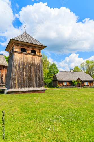 Tower of traditional wooden church in Tokarnia village on sunny spring day, Poland