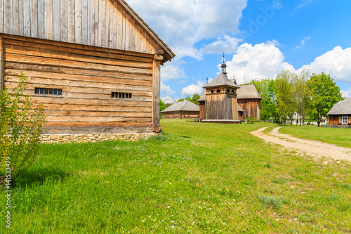 Wooden wall of traditional house in foreground with church in background, Tokarnia village on sunny spring day, Poland
