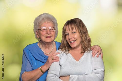 Poster Seniorin umarmt 40 jährige Frau vor grünem Hintergrund