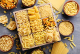 Different kinds of pasta on grey wooden table - 141542819