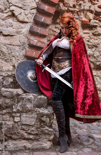 Warrior woman with sword in medieval clothes is very dangerous