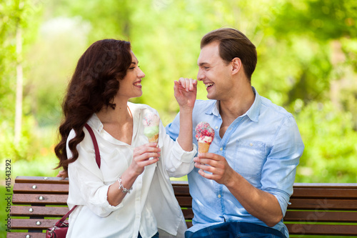 Poster Couple joking and having fun while eating an ice cream