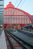 Antwerp Central train station pictured after a rainy day. The monumental red iron building structure is reflected in a puddle.
