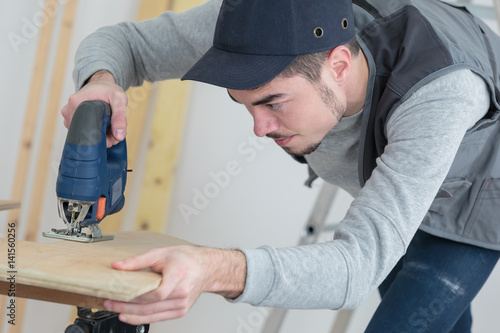 Poster Young man using electric jigsaw