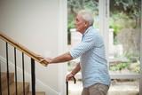 Senior man climbing upstairs with walking stick - 141571457