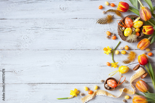 Easter wooden background with eggs, candy and flowers