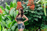 Fashion photo of beautiful tanned woman with brown hair in jeans shorts and black top Posing in Tropical Green Leaves