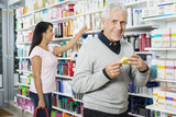 Senior Man Holding Product While Woman Shopping In Pharmacy