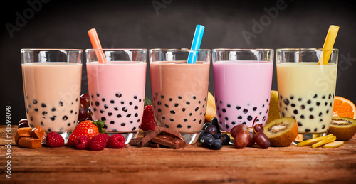 Row of fresh boba bubble tea glasses on wooden background Poster