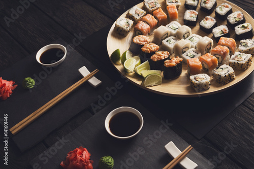 Póster Set of salmon sushi and rolls on black background, top view