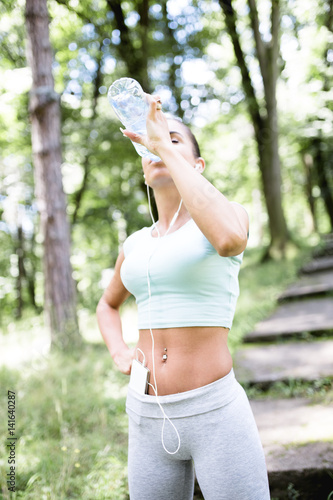 Attractive young woman with sunglasses walking or standing in city park after fitness activity and drinking water. Active life theme.