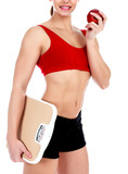 Smiling fit woman with scale and apple