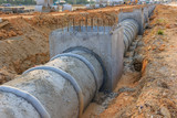 Concrete Drainage Pipe and manhole on a construction Site .Concrete pipe stacked sewage water system aligned on site - 141652264