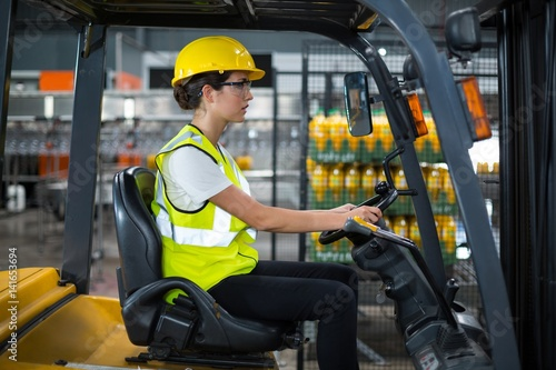 Poster Female factory worker driving forklift