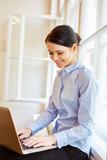 Junge Frau schreibt auf Laptop