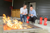 Men training with fire extinguishers - 141679239