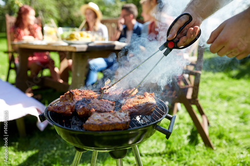 man cooking meat on barbecue grill at summer party - 141680265