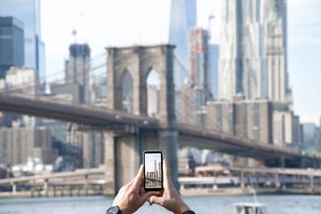 Tourist photographing Brooklyn Bridge, USA