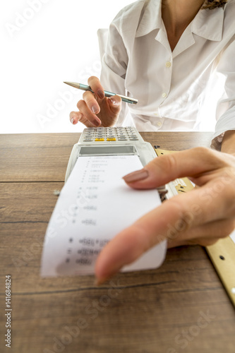 Woman doing accounting on a manual adding machine - 141684824