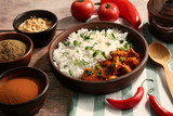 Bowl with delicious chicken tikka masala, rice and spices on wooden table