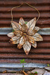 Rusty Old Metal Flower Hanging on a Galvanized Metal Wall