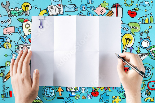 Hands ready to draw on a blank sheet of paper