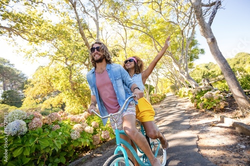 Poster Couple having fun while cycling in the park