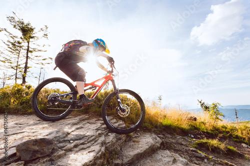 Woman riding mountain bike downhill