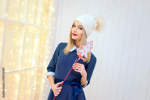 girl in a hat holding a Christmas tree on a stick Poster