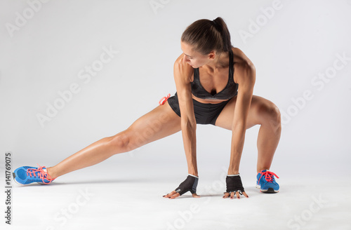 Poster muscular fit young woman doing stretching exercise isolated on studio background
