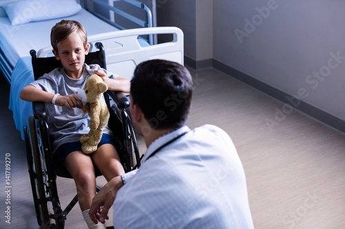 Fotografiet Male doctor interacting with child patient in ward