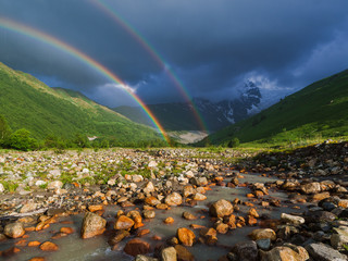 Summer landscape with a rainbow in the mountains