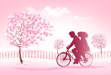 Couple riding a bike in a park.