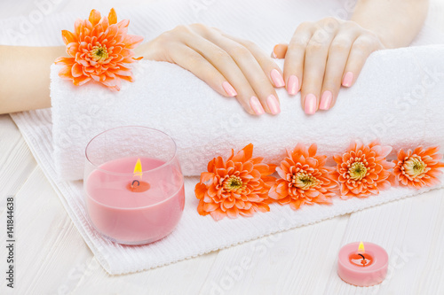 Fototapeta beautiful pink manicure with orange chrysanthemum and towel on the white wooden table. spa