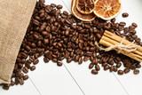 Granos de café, canela en rama y naranjas