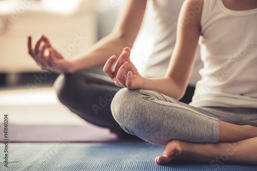 Leinwandbild Motiv Mom and daughter doing yoga