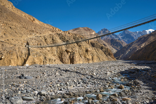 Suspension bridge over the river in Mustang region of Himalayas, Nepal Poster
