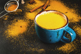 Traditional Indian drink turmeric milk is golden milk with cinnamon, cloves, pepper and turmeric. On a concrete table, with spices on the background. In mug, toned copy space - 141906499