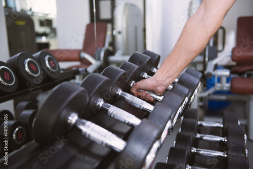 Hand of  man taking a dumbbell out of set of black weights
